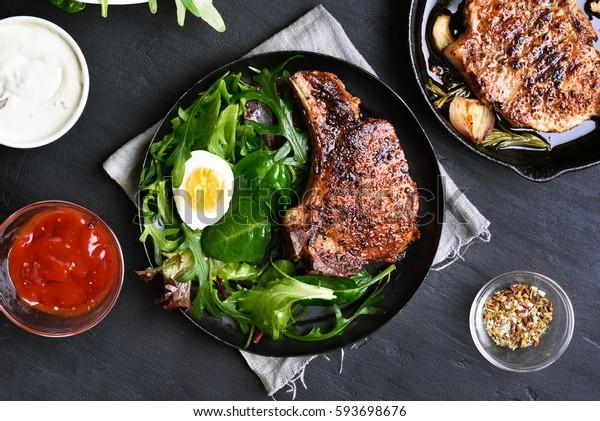 Grilled pork steak with green salad on dark background, top view