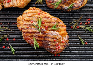 Grilled pork steak, pork neck with the addition of herbs and spices on the grill plate, top view, Grilled meat, bbq, barbecue