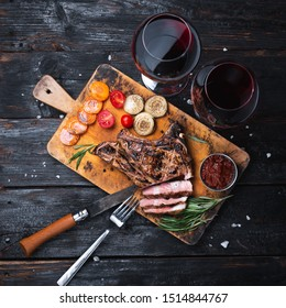grilled pork steak on a cutting board, delicious pieces of meat, a glass of red wine. Dinner for two