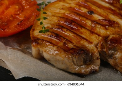 Grilled pork steak with tomato served thyme