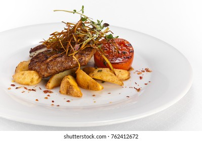 Grilled pork steak with vegetables and roasted potatoes on white background