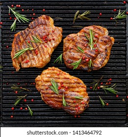 Grilled pork steaks, pork neck with the addition of herbs and spices on the grill plate, top view, Grilled meat, bbq, barbecue