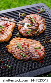 Grilled pork steaks, pork neck with the addition of herbs and spices on the grill plate, top view, close-up, outdoors. Grilled meat, bbq, barbecue
