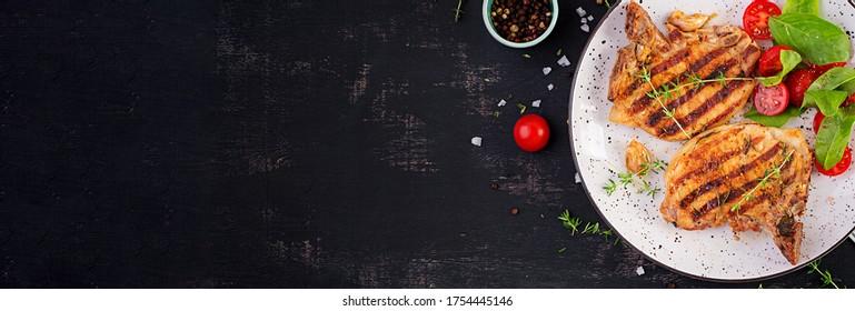 Grilltes Schweinefleisch, Steaks und Salat mit Tomaten auf dunklem Hintergrund. Draufsicht, Banner, Kopienraum