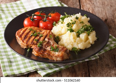 Grilled pork T-bone steak garnished with mashed potatoes and tomato close-up on a plate. horizontal
