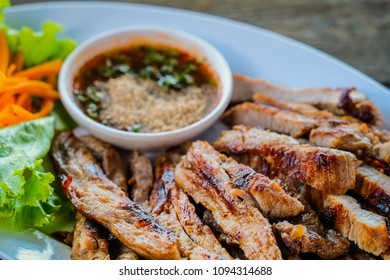 Grilled pork in a white dish with vegetables and dipping sauce on a wooden table.