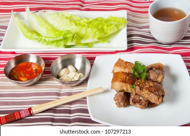 grilled pork wrapped with green leafy vegetables and fresh garlic