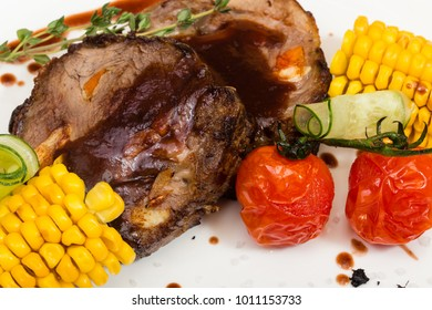 Grilled porky neck stuffed with garlic and carrot served with boiled corn and pickled tomatoes decorated by rosemary