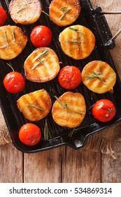 grilled potato halves and tomatoes with herbs macro on the grill pan. vertical view from above