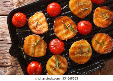 grilled potato halves and tomatoes with herbs macro on the grill pan. horizontal view from above