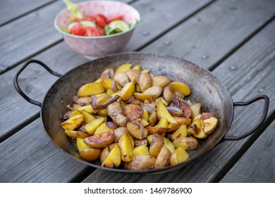 grilled potatos with onionin and salad iron pan