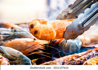 Grilled Prawns on the charcoal grill with tongs
