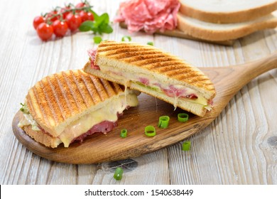 Grilled and pressed toast with Serrano salami, cheese, tomato and iceberg lettuce served on a wooden table