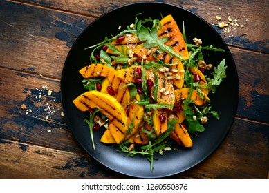 Grilled pumpking warm salad with arugula, walnuts and pomegranate seeds on a black plate over dark wooden background.Top view with copy space.
