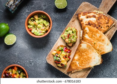 Grilled quesadillas (tortillas with cheese) on wooden board and two spicy dips: pineapple salsa and guacamole. Dark background, top view. Mexican cuisine concept