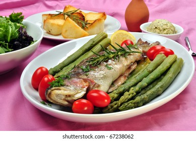 grilled rainbow trout with asparagus on a plate