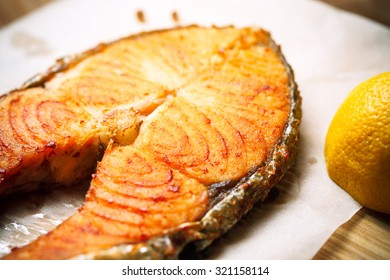 Grilled red fish steak salmon on paper, vertical top view close-up