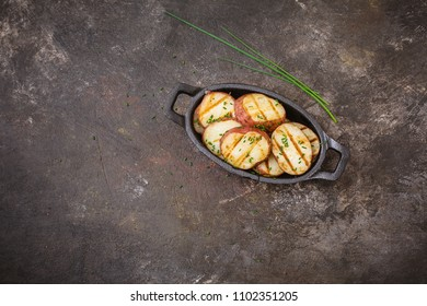 Grilled Red Potatoes in a Cast Iron Dish with Chives on a Dark Background