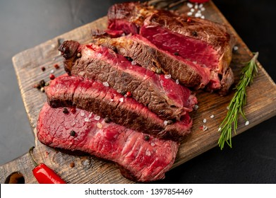 Grilled rib eye beef steak with herbs and spices on a stone background