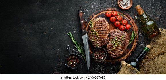 Grilled ribeye beef steak, herbs and spices on a dark table. Top view. Free space for your text.