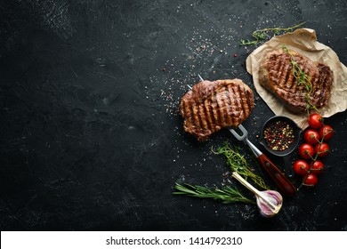 Grilled ribeye beef steak on the fork. At the aged table. Top view. Free space for your text.