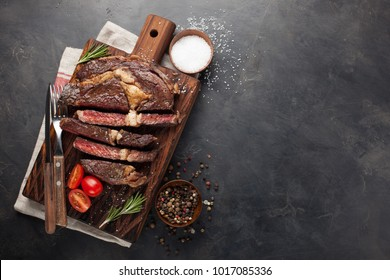 Grilled ribeye beef steak with red wine, herbs and spices on a dark stone background. Top view with copy space for your text