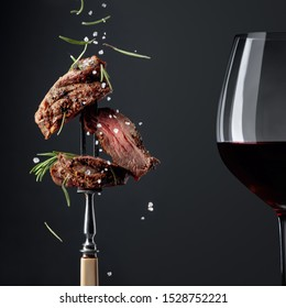 Grilled ribeye beef steak with rosemary and red wine on a black background. Beef steak on a fork sprinkled with rosemary and sea salt.