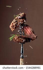 茶色の背景に焼きビーフステーキとローズマリー。フォークにローズマリーと塩を振りかけたビーフステーキ。