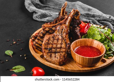 Grilled Ribeye Steak on bone and vegetables with fresh salad and bbq sauce on cutting board over black stone background. Hot Meat Dishes