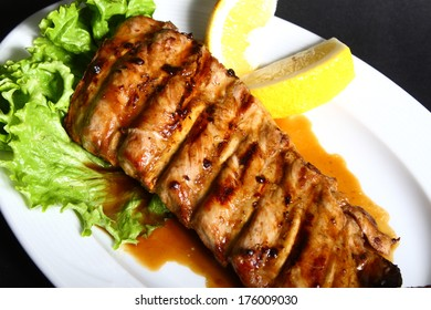 Grilled ribs with vegetables on white plate