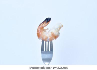 grilled river shrimp stabbing by silver fork on white background