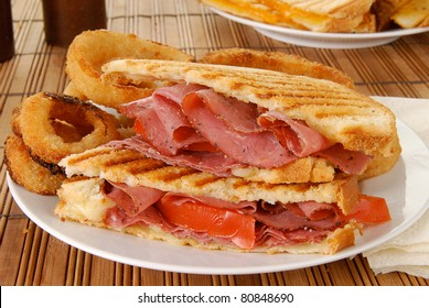 A grilled roast beef sandwich with onion rings