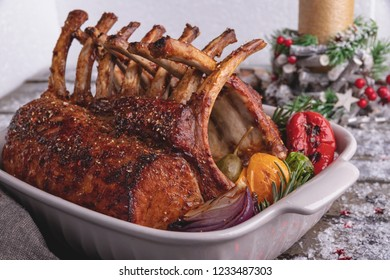 Grilled roasted rack of lamb chops with vegetables in ceramic baking dish. New Year christmas composition,decoration.