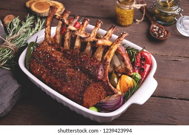 Grilled roasted rack of veal lamb chops with vegetables in ceramic baking dish.