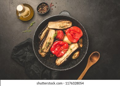 Grilled or roasted vegetables on a pan. Oven roasted eggplant, pepper, tomato, onion, garlic with olive oil and thyme. Top view, toned image