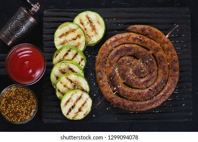 Grilled rolled sausage with zucchini, ketchup and mustard on a black wooden serving board, above view
