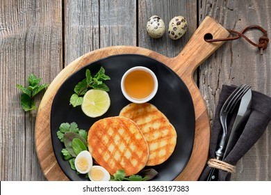 Grilled round slices of Greek cheese with honey, green salad and quail egg. Flat lay on rustic wooden table.