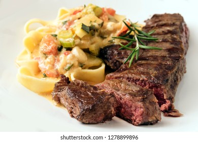 Grilled rump steak with vegetable sauce and pasta on a light gray background, selected focus, narrow depth of field