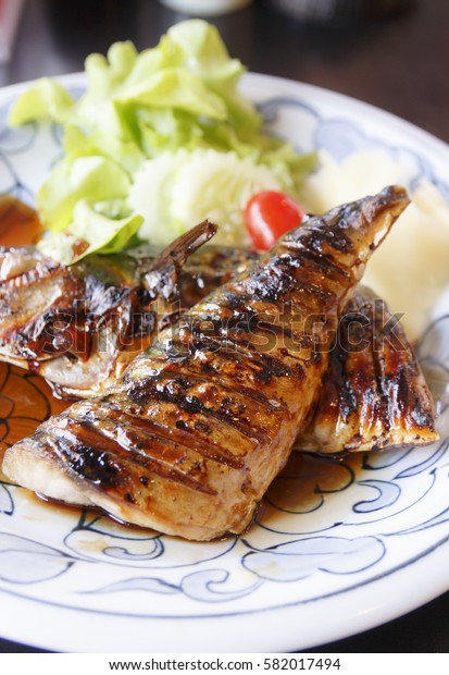 Grilled saba fish in teriyaki sauce on white dish