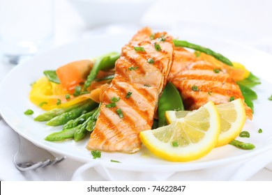 grilled salmon with asparagus, pea, yellow peppers, carrots and spring onions on white plate