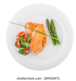 Grilled salmon with asparagus and vegetables isolated on white background. Clipping path