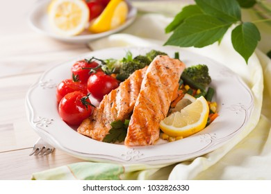 Grilled salmon with broccoli, tomatoes, beans and corn on a white country-style plate