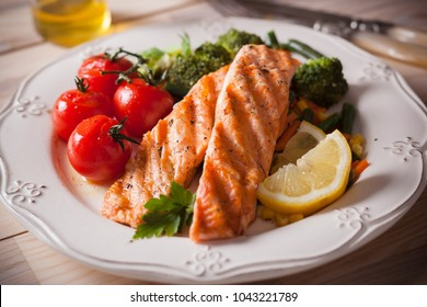 Grilled salmon with broccoli, tomatoes, beans and corn on a white plate.