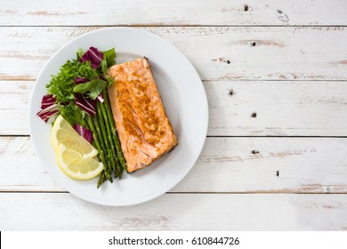 Grilled salmon fillet with asparagus and salad in plate on white wooden table