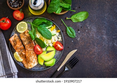 Grilled salmon fillet with couscous, salad fresh vegetables and avocado on dark background. Top view flat lay. Copy space.