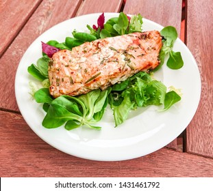 Grilled salmon fillet with fresh green salad, soft focus