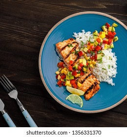 Grilled salmon fillet with fruit sauce made of mango, bell pepper, onion and avocado with basmati rice garnish on a blue plate. Delicious seafood meal. Top view shot above.