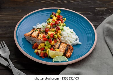 Grilled salmon fillet with fruit sauce made of mango, bell pepper, onion and avocado with basmati rice garnish on a blue plate. Delicious seafood meal on a table.