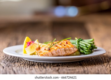 Grilled salmon fillet with lemon and green beans.
