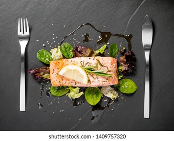 Grilled salmon fillet with salad on black slate plate